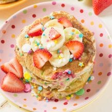 Strawberry Banana Protein Pancakes- Light & fluffy protein buttermilk pancakes filled with strawberries, bananas and sprinkles that not only taste delicious but keep you full until lunch!