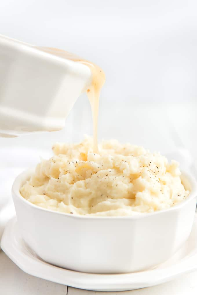 turkey gravy being poured on mashed potatoes