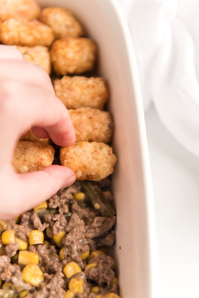 layering tater tots on top of tater tot casserole
