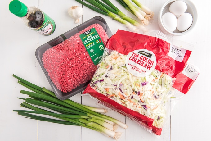 The ingredients for this egg roll inspired dinner are presented on a white surface.