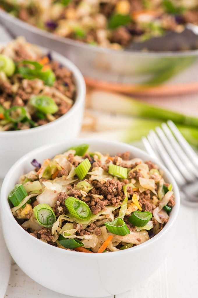 Two bowls of egg roll in a bowl are placed next to each other on a white surface.