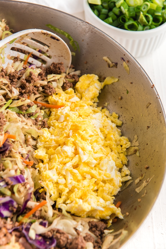 Scrambled eggs are in the corner of a skillet.