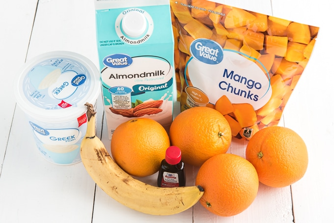 The ingredients for the smoothie are laid out on a white surface.