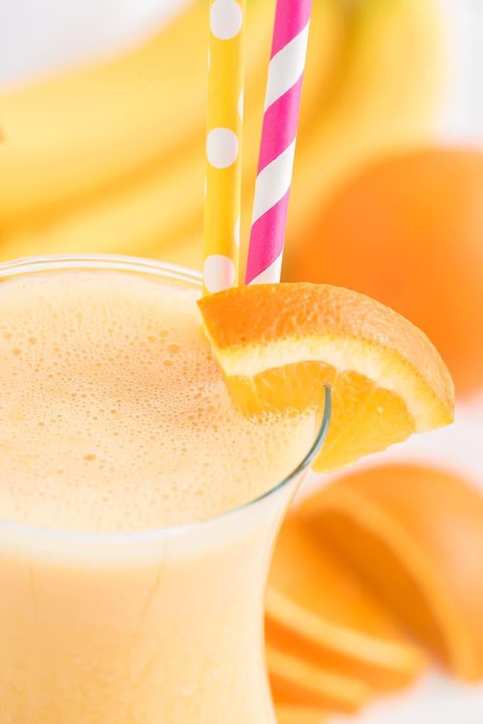 An orange slice is garnishing a glass of orange smoothie.