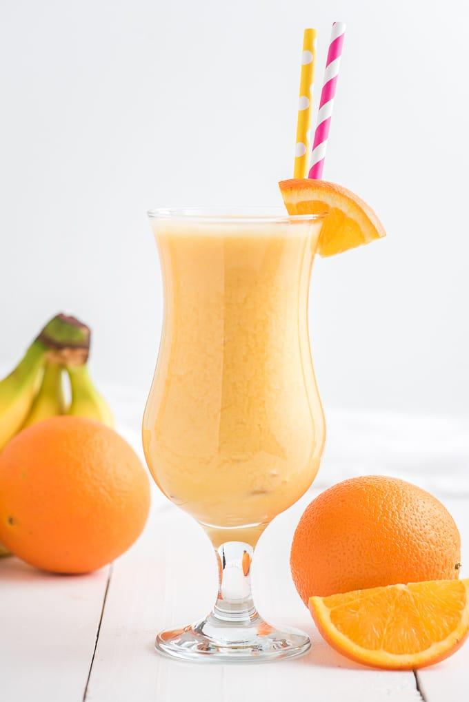 An orange smoothie is served in a daiquiri glass.