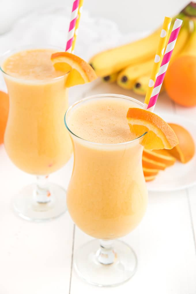 Two glasses are filled with orange smoothie.