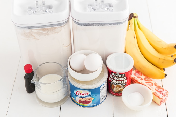 The ingredients for banana cake are presented on a white surface.