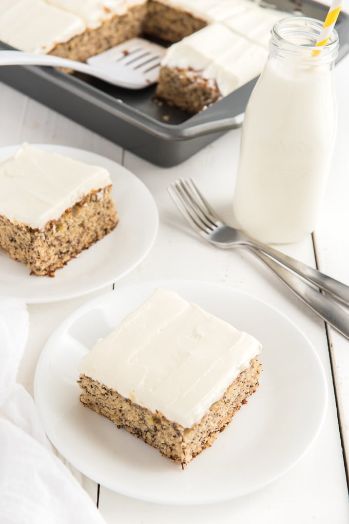 Two slices of banana cake are presented on white plates, next to a pint of milk.