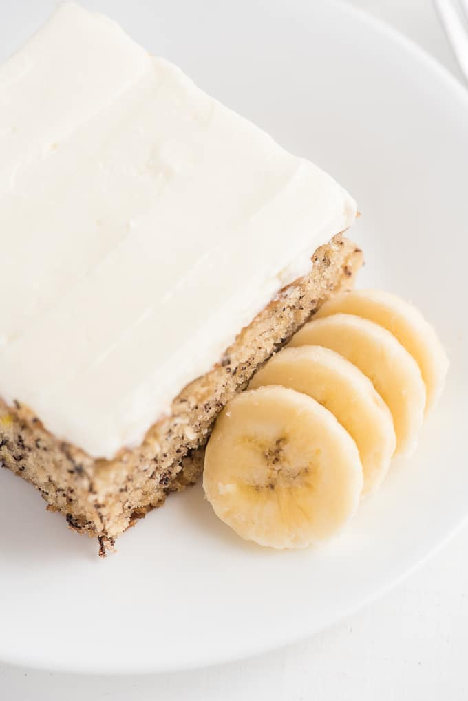 A sliced banana is placed next to a piece of banana cake.