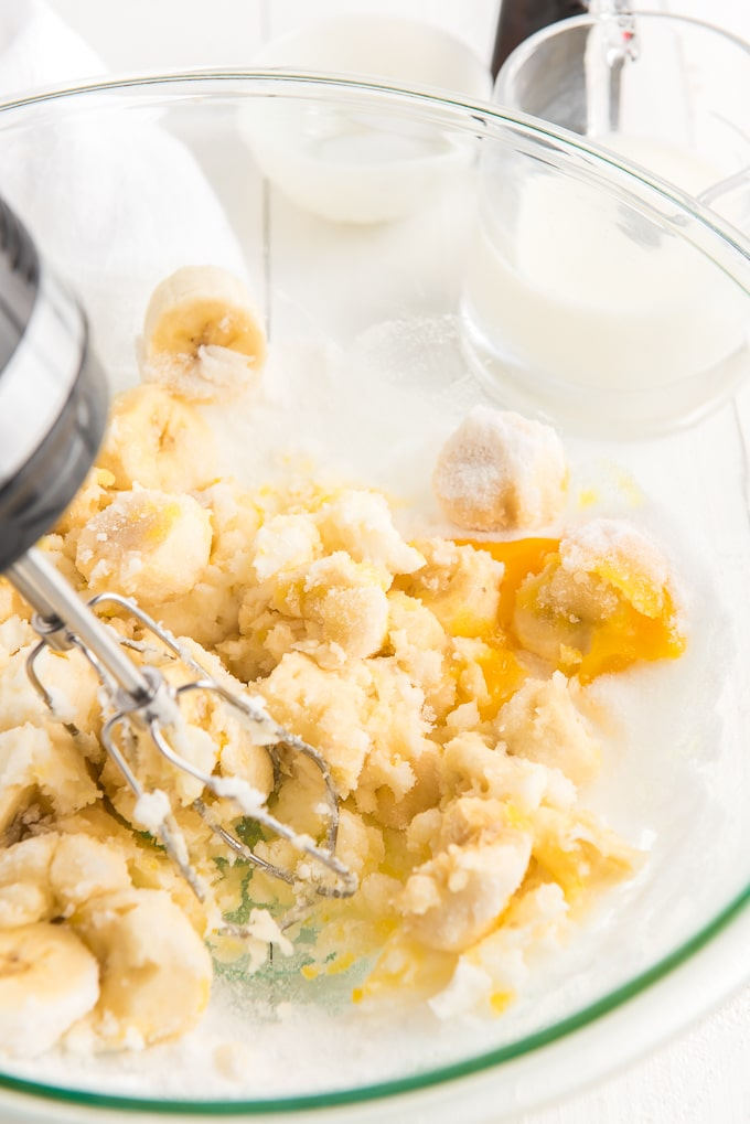The ingredients are being creamed together by an electric mixer in a large glass bowl.