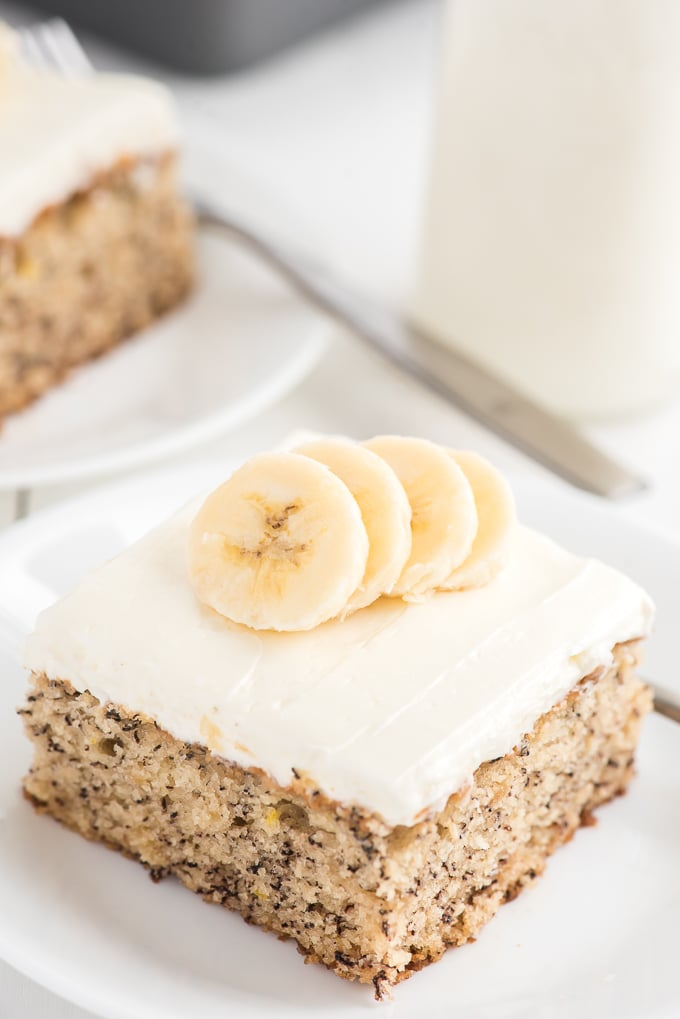A slice of banana cake is presented on a white plate.