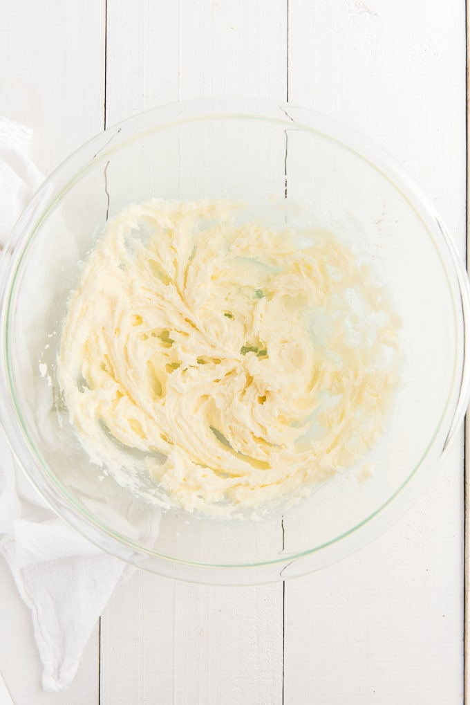 A glass bowl contains a creamed mixture.