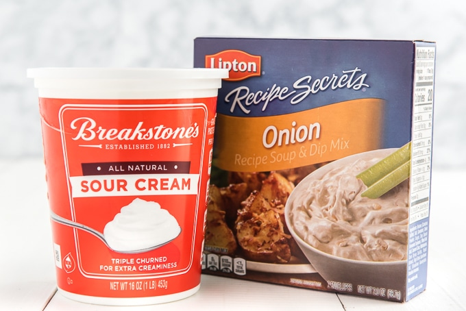 The ingredients for French onion dip are presented on a white countertop.
