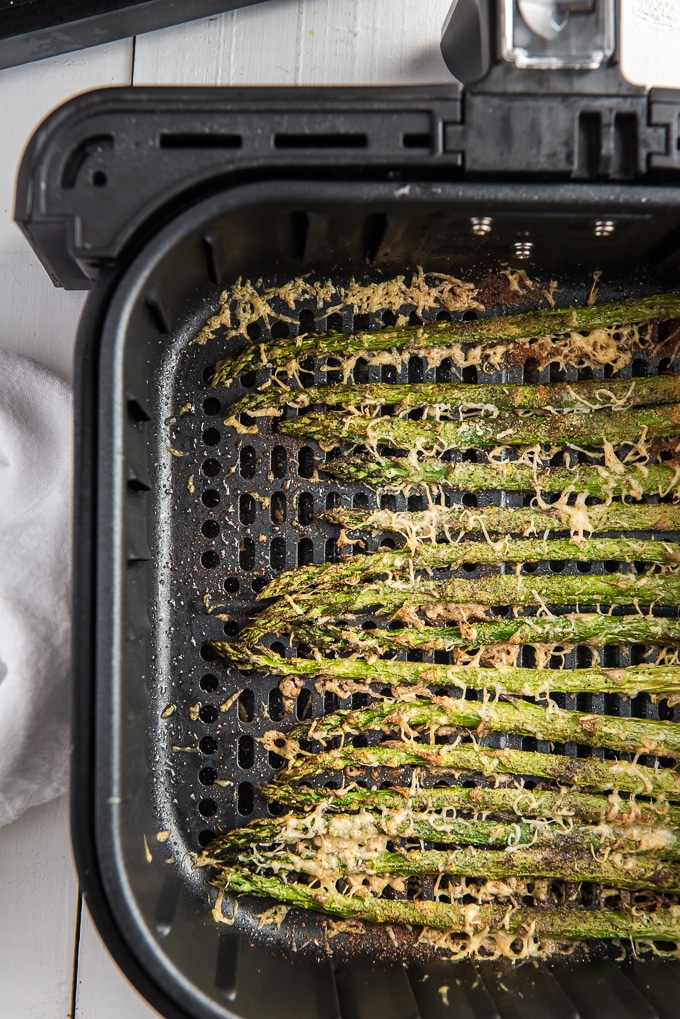 Asparagus topped with cheese is fully cooked in an air fryer.