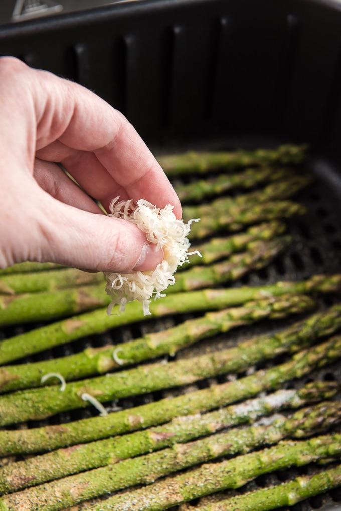 Cheese is being sprinkled over uncooked asparagus in an air fryer basket.