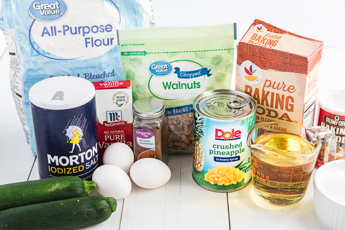 The ingredients for pineapple zucchini bread are placed on a white surface.