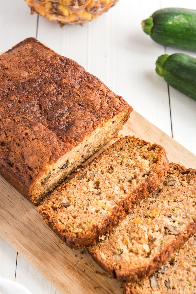 A loaf of pineapple zucchini bread has been sliced into.