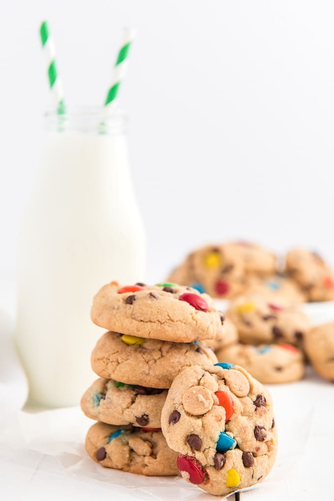A stack of cookies is placed in front of a jug of milk.