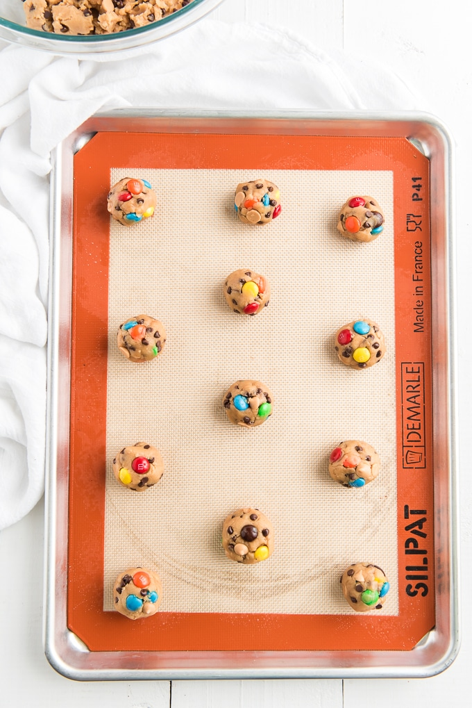 Cookie dough balls are spread out on a prepared baking sheet.