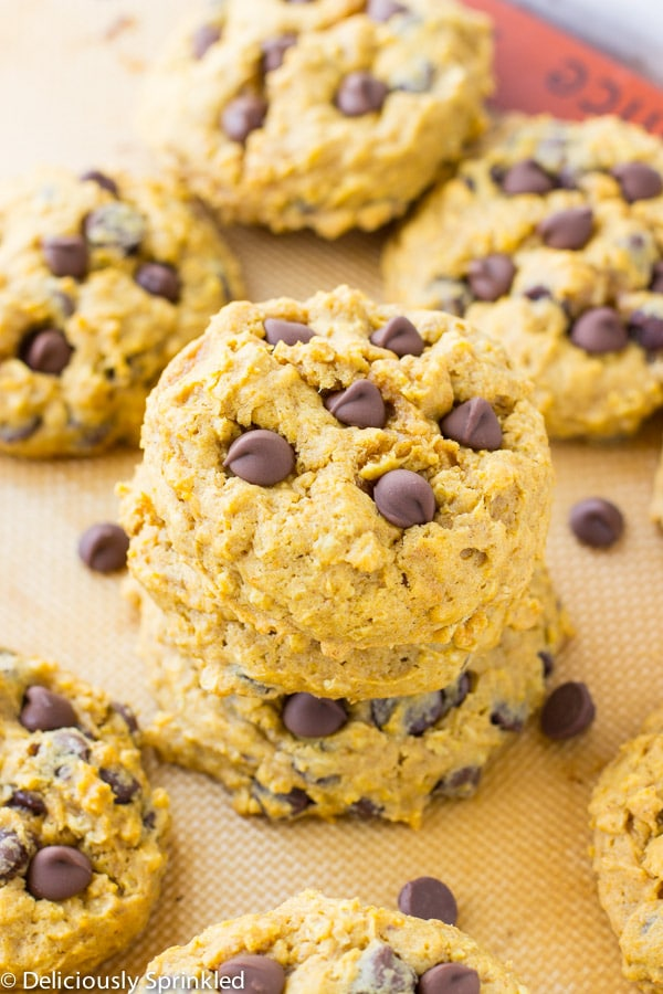 Several pumpkin chocolate chip cookies are stacked on top of one another.