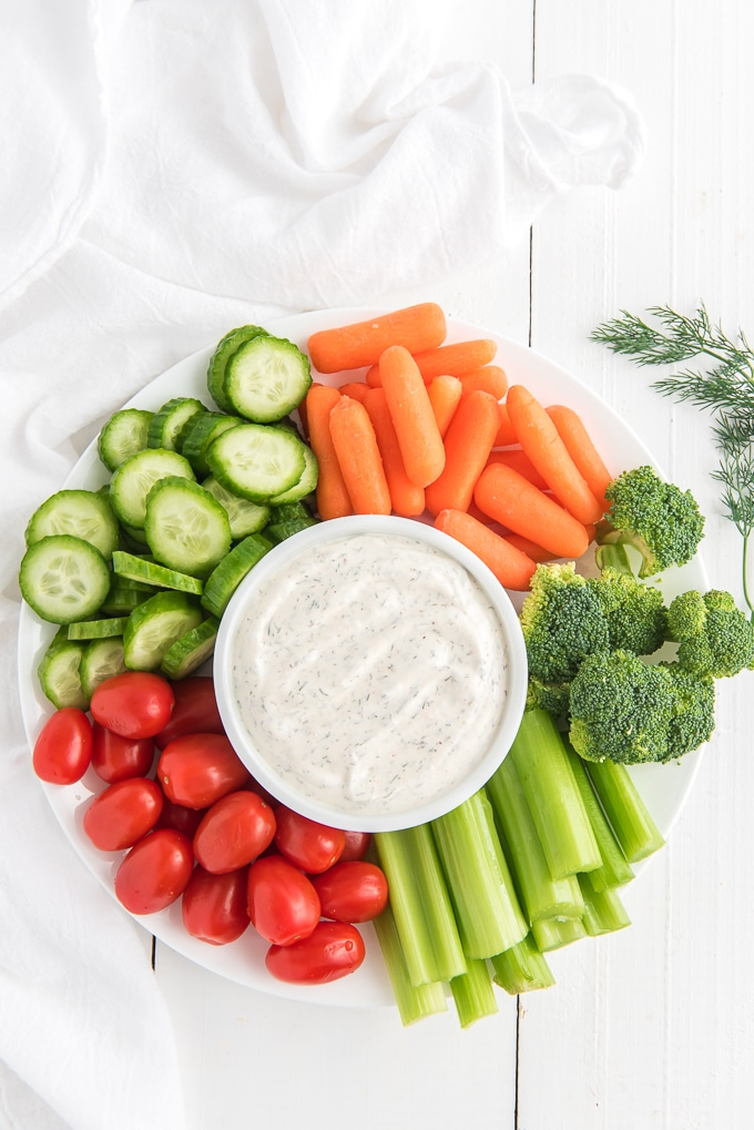 Veggies are placed around a small white bowl of dip.