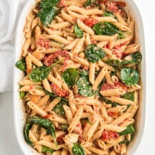 Pasta is stirred with baby spinach in a white baking dish.