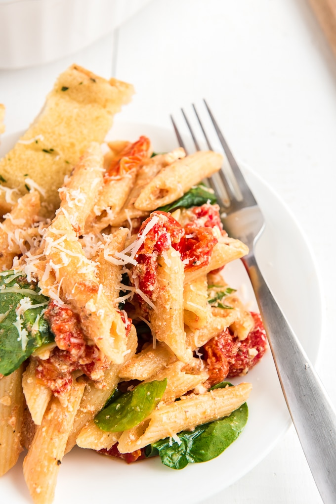Penne noodles are tossed in baked feta cheese and tomatoes on a plate.