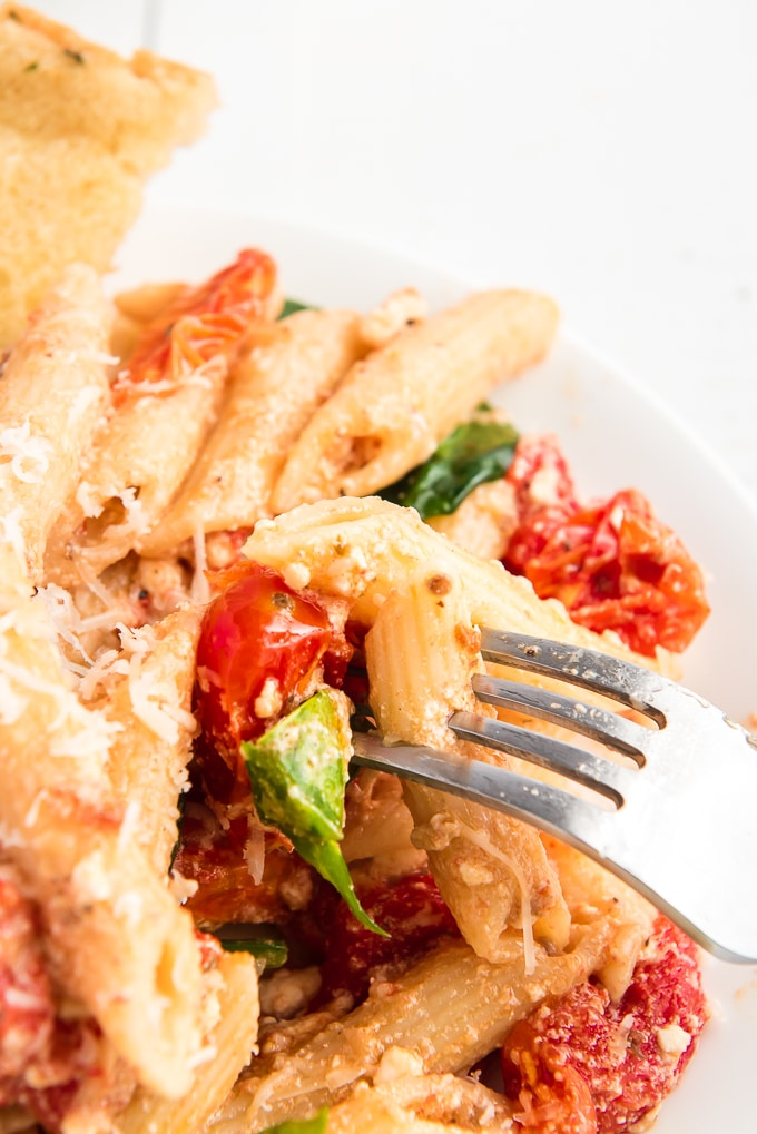 A fork is lifting a piece of pasta from a plate.