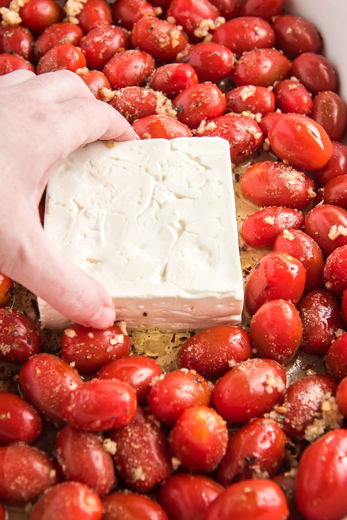 A block of feta cheese is placed in the middle of a baking dish with tomatoes and olive oil.
